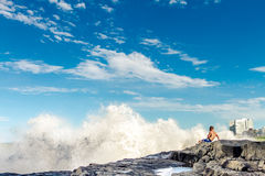 Man rests on a rock in breaking waves on a beach Royalty Free Stock Photography