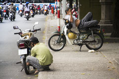 Man rests on scooter in Ho Chi Minh City, Vietnam Stock Photos
