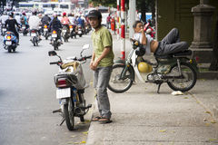 Man rests on scooter in Ho Chi Minh City, Vietnam Royalty Free Stock Photos