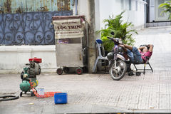 Man rests on scooter on street of Ho Chi Minh City, Vietnam Stock Images