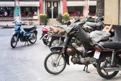 Man rests on scooter on street of Ho Chi Minh City, Vietnam Stock Photo