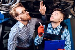 Man on the result of the work of a mechanic. The client evaluates the repair of the car by a mechanic.  royalty free stock images
