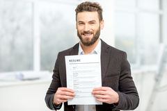 Man with resume paper. Elegant man in the suit holding resume for job hiring in the bright interior royalty free stock photos