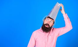 Man with retarded face and long beard wearing silver paper bag on his head, madness concept. Shopaholic undergoing. Medical treatment. Bearded man with mental Royalty Free Stock Image
