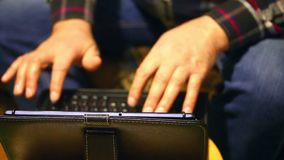 A man of retirement age is uncertain, with two hands typing notes in the tablet. The tablet is on a stand, on a chair. A man of retirement age is uncertain stock video footage