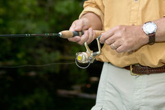 Man retrieving a lure while freshwater fishing. Winding in the line on his reel in a close up view of his hands Stock Photography