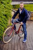 A man on a retro bicycle in a park. Redhead bearded male dressed in a blue jacket and jeans on a retro bicycle in a park stock photography