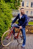 A man on a retro bicycle in a park. Redhead bearded male dressed in a blue jacket and jeans on a retro bicycle in a park royalty free stock photography