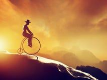 Man on retro bicycle riding downhill. Mountains stock illustration