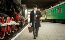 Man in retro suit with suitcase walking on the train platform Royalty Free Stock Images