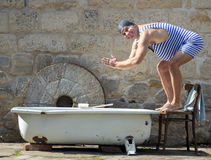 Man in retro swimsuit. Jumps to the outdoor bathtub royalty free stock photos