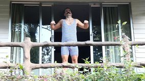 Man in retro swimsuit trains on the balcony stock video footage