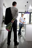 A man returning home to his family after work, holding a bunch of roses Stock Images