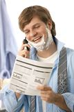Man reviewing document while shaving Stock Photos