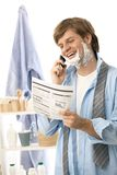 Man reviewing document while shaving Royalty Free Stock Photos