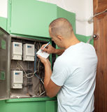 Man rewrites electric meter readings. At house Royalty Free Stock Photo