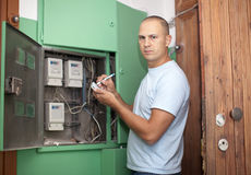 Man rewrites electric power meter readings. At house Royalty Free Stock Photos