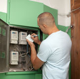 Man rewrites the meter readings. Man rewrites the electrical meter readings Stock Image