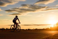 A man ride a bicycle at sunset with sunbeam Stock Image