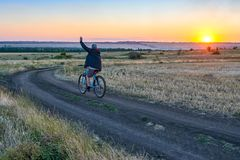 Man ride a bike in the country on the field in the evening Stock Images