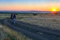 Man ride a bike in the country on the field in the evening Stock Photography