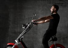 Man ride new electric car motorcycle bicycle scooter in black cloth shout out loud on concrete wall. Background surprised royalty free stock images
