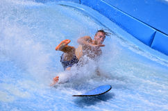 Man ride a surfing board on FlowRider. GOLD COAST OCT 29 2014: Man falling from a surfing board on FlowRider. It is a water park attraction that simulate the Royalty Free Stock Images