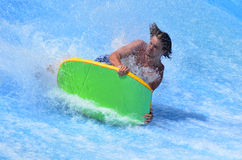Man ride a surfing board on FlowRider Stock Photos