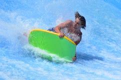 Man ride a surfing board on FlowRider Stock Photos