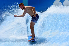 Man ride a surfing board on FlowRider. GOLD COAST OCT 29 2014: Young man ride a surfing board on FlowRider. It is a water park attraction that simulate the Stock Photography