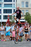 Man ride unicycle during a street performance Royalty Free Stock Image
