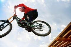 Man rider drops on jump. Mountain biking in sunlight Royalty Free Stock Photo