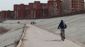 A man rides a Bicycle along a concrete road near the pond, Royalty Free Stock Photos