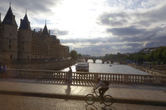 A man rides a bicycle over the River Seine, in Paris, France, AUGUST 5, 2015 Royalty Free Stock Photo