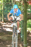 Man rides bicycle on tightrope at hight rope course Stock Photography