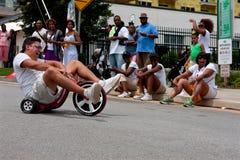 Man Rides Big Wheel Tricycle Downhill On Atlanta Street. Atlanta, GA, USA - August 3, 2013: An unidentified man rides downhill on a Big Wheel at the Cool Dads stock photos