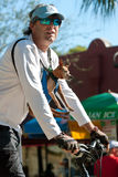 Man Rides Bike With Small Dog Strapped To Chest Royalty Free Stock Image