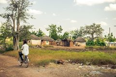 Man rides his bicycle in Africa. A man rides his bicycle in a village in Ghana stock photo