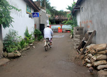 Indonesian Village. A man rides his bicycle through the streets of a quiet village in Gili Trawangan, Indonesia Royalty Free Stock Photography