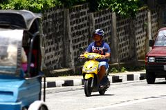 A man rides his scooter on an uphill road in Antipolo City. Stock Photo