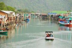 Man rides motorboat by the fishermen village in Sam Roi Yot National park, Sam Roi Yot, Thailand. SAM ROI YOT, THAILAND - MARCH 30, 2012: Unidentified man rides Stock Images