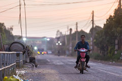 Man rides on old motorbike down the road at the Muslim district Stock Photo