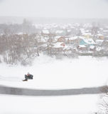 Man rides Quad bike along river village in winter. A man rides a Quad bike along the river to the village in winter Stock Photos