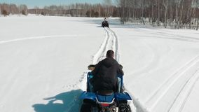 A man rides a quad making a maneuver for a woman. A man rides a quad making a maneuver for a woman - Aerial view stock video