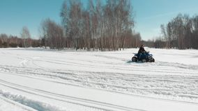 A man rides a quad in the snow and reaches the woman. Aerial stock footage