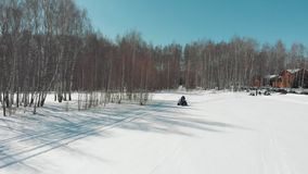 A man rides a quad with a woman on a snowy field. Wide angle stock footage