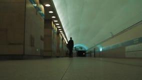 Man rides skateboard at empty underground metro station. SAINT PETERSBURG, RUSSIA -  SEPTEMBER 28, 2017: Man in black clothes rides skateboard at empty stock footage