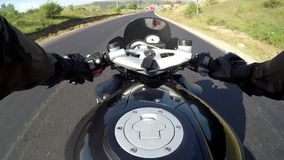 The point of view of a motorcycle. A man rides a sports bike on the road stock video