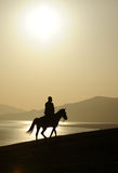 Man Ridig Horse At Sunrise Stock Images