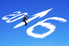 Man riding 2016 arrow up shape clouds in blue sky Stock Image